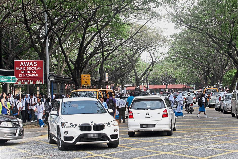 Motorists exiting from the commercial area next to SMK Kota Kemuning still drive against traffic despite the implementation of the one-way system.