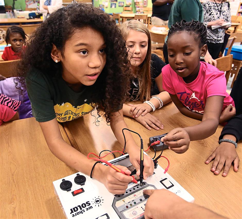 Power pack: Fifth grader Nemiah Wallace (left) tests the electronics of a 'solar suitcase'. The solar suitcases, which use a solar panel to generate electricity, will be sent to orphanage schools in Uganda. — TNS photos
