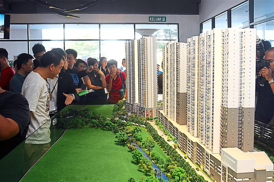 Towering residence: Visitors and property hunters looking at a model of Parkhill Residence at the company's showroom in Street Mall One South, Seri Kembangan.