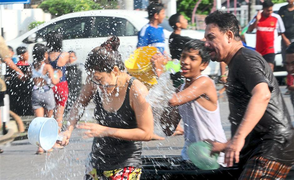 Water play: Residents having a wonderful time splashing water at each other.