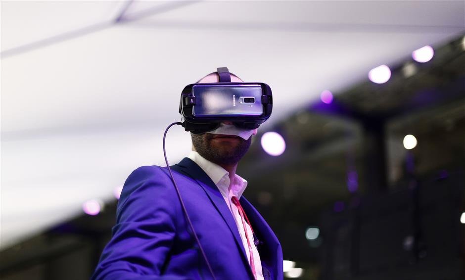 A visitors uses a VR gear installed on a new Samsung Galaxy S9 mobile phone during the Mobile World Congress wireless show, in Barcelona, Spain, Tuesday, Feb. 27, 2018. The annual Mobile World Congress (MWC) runs from 26 February - 1 March and draws over 2,300 exhibitors to Barcelona, including industry heavyweights Samsung, Huawei and Nokia. (AP Photo/Manu Fernandez)