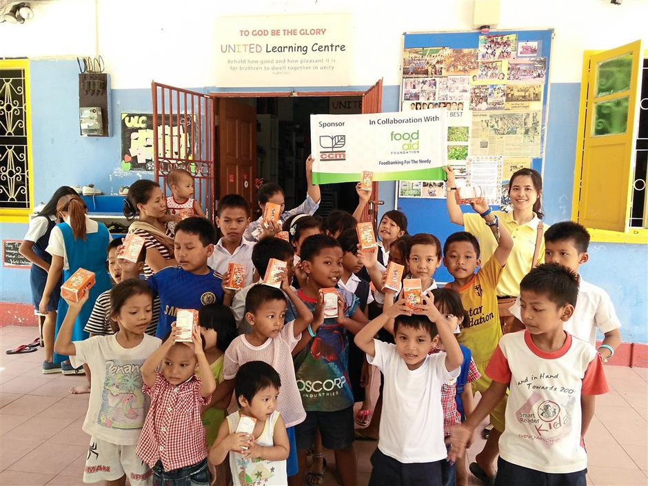 Diverse work: Vietnamese student Ngo Thi Thu Hong (back row, right, in yellow) helping to distribute food packages and vitamins donated by a corporate sponsor during one of Food Aid Foundations visits.