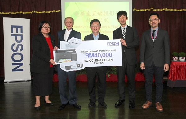 Chow (middle) witnessing the presentation of teaching equipment worth RM40,000 from Epson at SJKC Eng Chuan. With him are (from left) Lim, Tan, Hori and Sohire. (Left pic) A teacher at the school using Epson's interactive projector for a more interactive classroom experience.