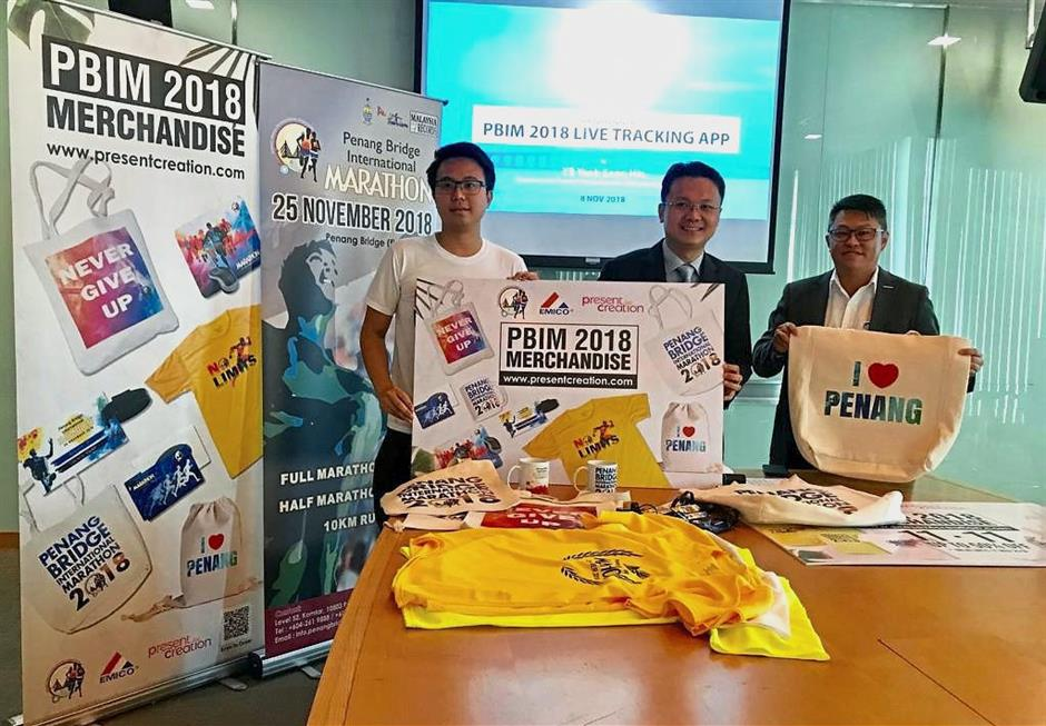 (From right) IJM Land Bhd (northern region) general manager Datuk Toh Chin Leong, Yeoh and EMICO Penang Sdn Bhd business development executive Vincent Tan showing PBIM merchandise and mementos during the launch of the app.