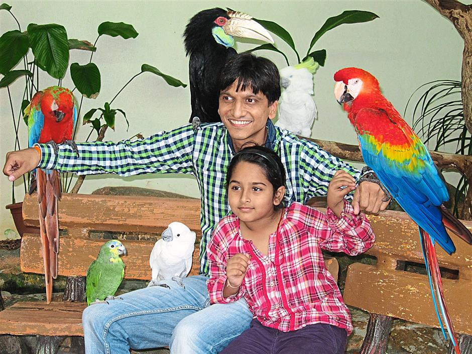 Two siblings posing for photos with some of KL Bird Park's colourful residents.