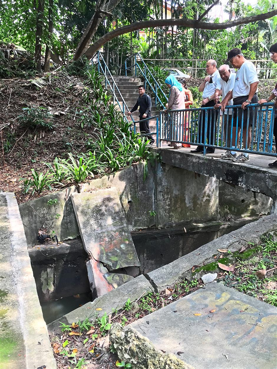 Gauging the damage: Residents looking at the wall barricade that collapsed into a storm drain at the Taman Aman park.