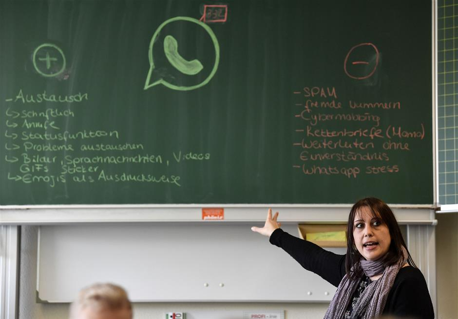 Teacher Vera Servaty talks to pupils during a lesson in social media and internet, at a comprehensive school in Essen, Germany, Monday, March 18, 2019.  Children feel stressed when dealing with the digital world, but Germany has taken a hands-on approach, with experts and teachers saying teenagers teaching younger school mates how to deal with digital stress, messaging and cyber-bullying have proven to be especially successful. (AP Photo/Martin Meissner)