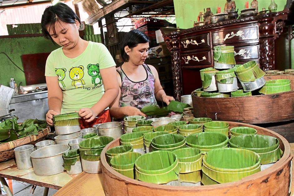Family operation: Cheang (right) wiping the banana leaves before daughter Hui Mian lines the tins with the leaves at their house in Lengkok Burmah, Pulau Tikus.
