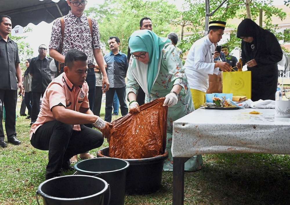 Tunku Azizah helping to dye a fabric at the workshop.