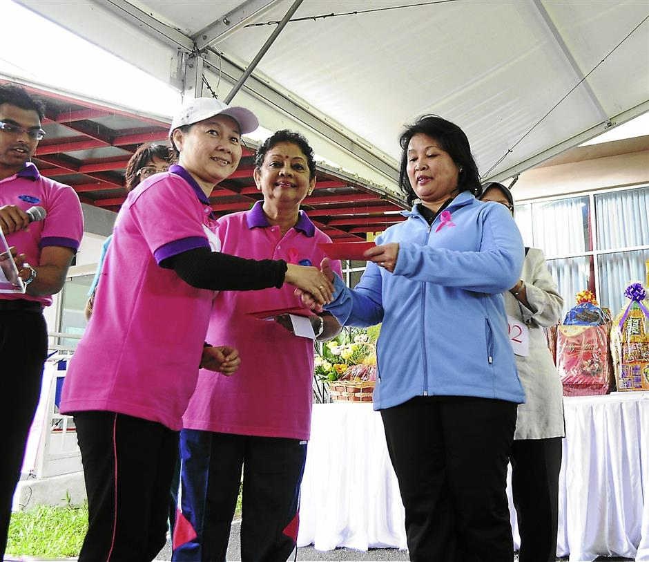 Padma Menon (cnetre) of the Breast Cancer Support Society Negeri Sembilan giving out prizes to a jogathon participant last year.