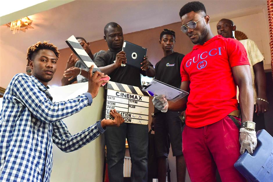 Participants pose during a workshop about filming with a smart-phone on March 30, 2019 as part of the 2nd edition of the Bushman Film Festival, the first Francophone film festival in West Africa focused of smart-phone filming, in Abidjan. - The second edition of the Bushman Film Festival ended on March 31, 2019. The event aimed at promoting new talents in the movie sector. In fact 5,000 films of which 350 were broadcasted during the festival and five categories of awards were attributed. (Photo by ISSOUF SANOGO / AFP)
