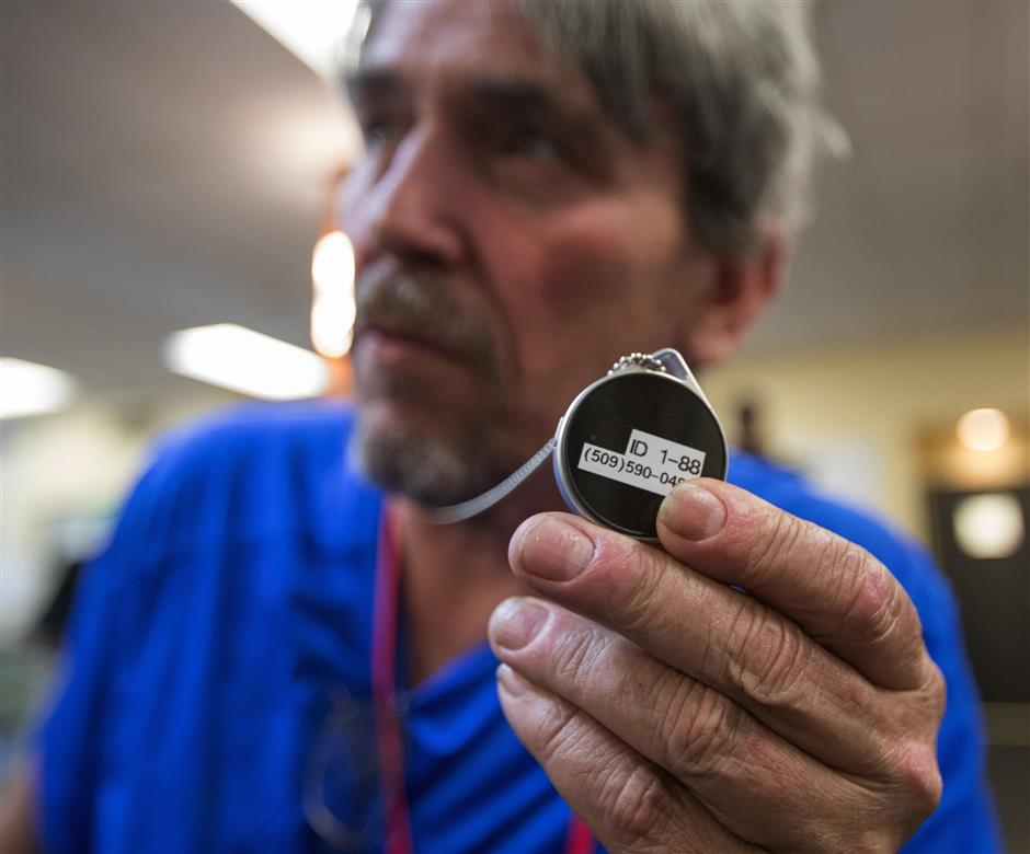John Kenny, 60, who is homeless, holds his 'beacon' from the Samaritan App company at the Millionair Club in Seattle on May 4, 2018. The Bluetooth-enabled device provides a cashless way to give directly to homeless people, via a smartphone app. (Steve Ringman/Seattle Times/TNS)