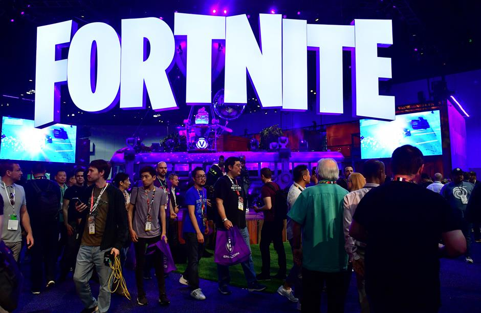 People crowd the display area for the survival game Fortnite at the 24th Electronic Expo, or E3 2018, in Los Angeles, California on on June 12, 2018, where hardware manufacturers, software developers and the video game industry present their new games. / AFP PHOTO / Frederic J. BROWN