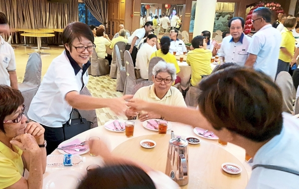 Nice to meet you: Chew shaking hands with party members during the general meeting.