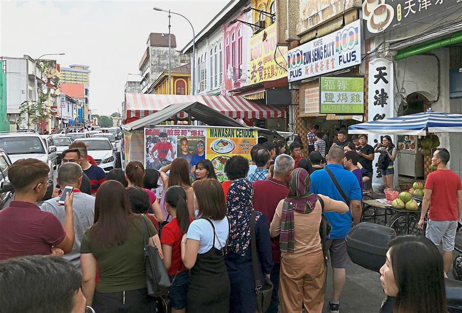 A file image of people queuing up to taste Ipohu2019s famous delicacies on Jalan Bandar Timah in Ipohu2019s old quarter. AirAsiau2019s flights will boost tourism in the state.