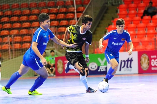 Mohamad Haris (centre) fending off two Chinese players in the play-off for fifth and sixth placing.