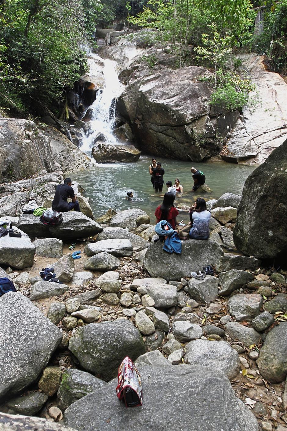 Picnickers taking a dip at the Titi Kerawang waterfalls.