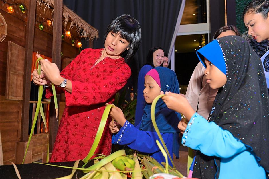 Rafidah sharing ketupat weaving with the kids during the Raya do.