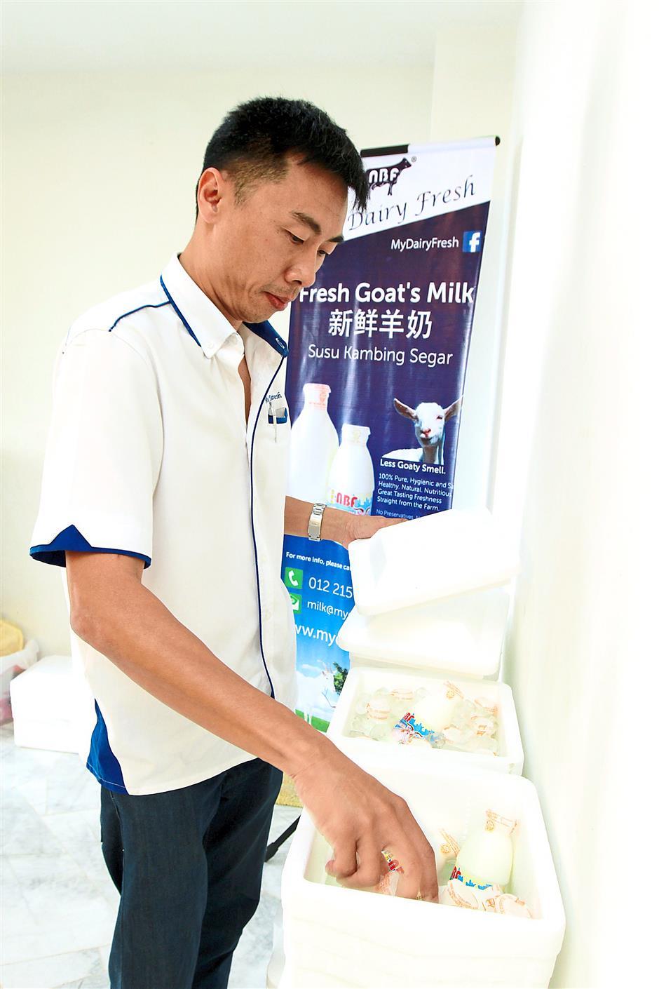 Organising his stock: Lai storing bottles of goat's milk in ice boxes.