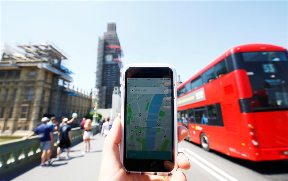 A photo illustration shows the Uber app and a bus in London, Britain, June 25, 2018. REUTERS/Henry Nicholls/Illustration