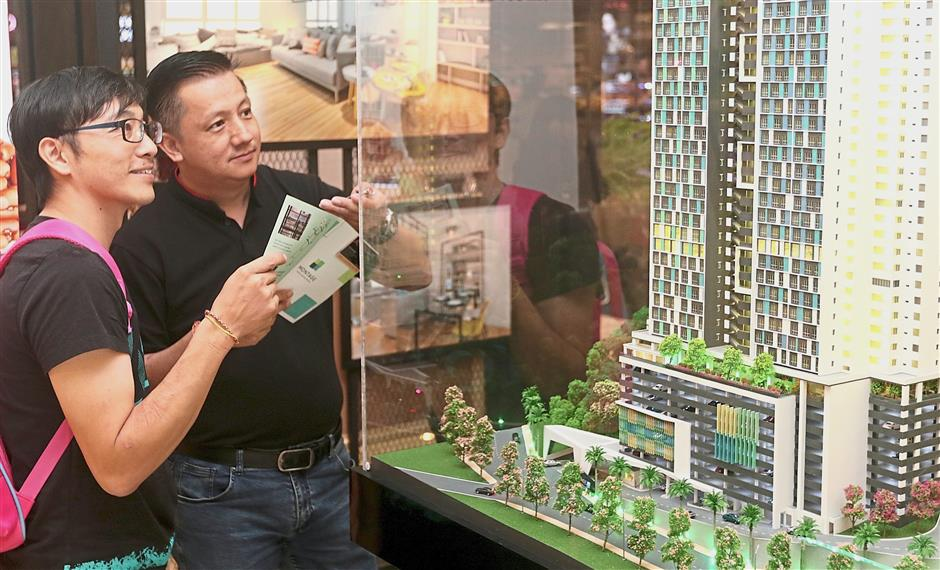 GIC Group project sale executive Yeap Tan Kheng (right) showing the scale model of the Montage project to visitor Philips Wen, 37, at the Pearl Ocean booth.