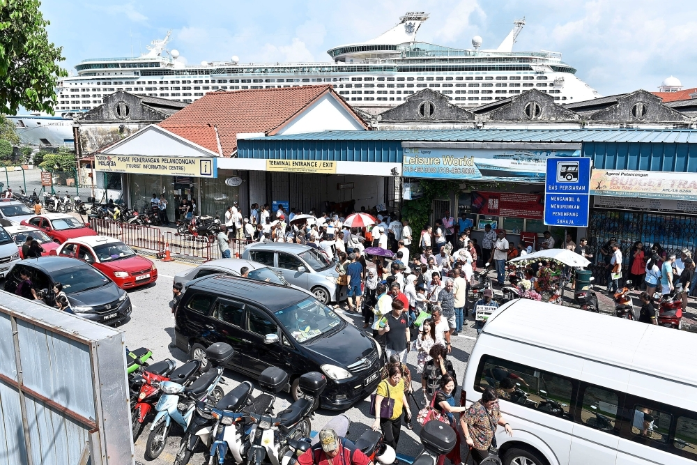 A filepic showing cruise passengers pouring out of Swettenham Pier from the 15-deck Voyager of the Seas in the background.
