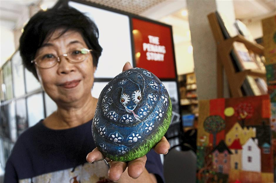 Ruth Yong showing a stone paintings in the Artisan Market and Garage Sale at The Star Pitt St in George Town.