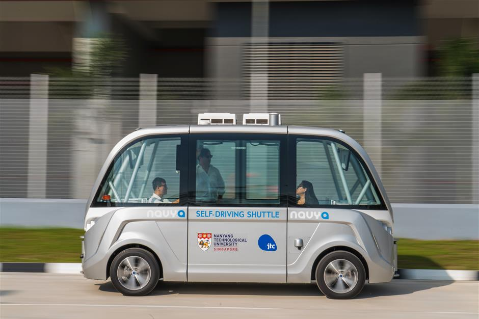 A Navya SAS autonomous electric passenger bus travels along the test circuit at the Centre of Excellence for Testing & Research of Autonomous Vehicles (CETRAN) of Nanyang Technology University in Singapore, on Tuesday, May 22, 2018. In the race to deploy driverless public transport, Singapore has built a mini town that could vault it into pole position. The 2-hectare complex, unveiled in November, has intersections, traffic lights, bus stops and pedestrian crossings, all built to the specifications that Singapore uses for its public roads. Photographer: Nicky Loh/Bloomberg