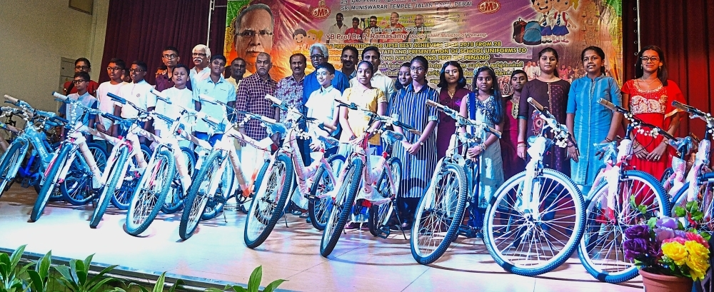 Some of the recipients with their bicycles posing for a group photo with Gopalakrishnan (checked shirt), the temple committee and guests at the temple hall.