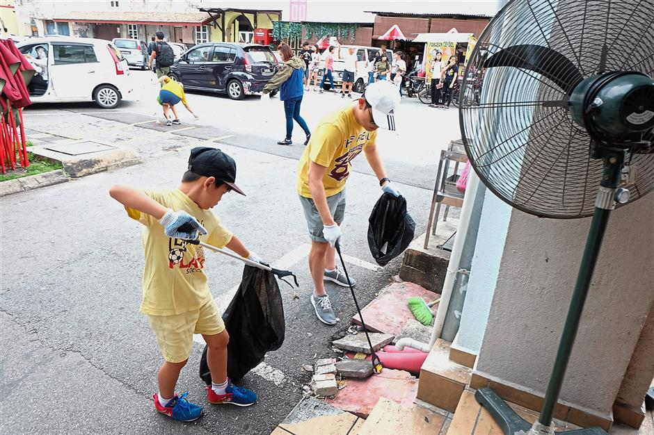 A young boy seen picking up rubbish that strewn on the street in the Old Town area.