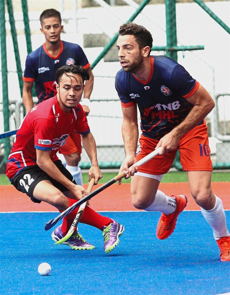 Back off: TNB Thunderbolt's Muhammad Hafizal Halmi (left) vying for the ball with UniKL's Valentin Verga during the Malaysia Hockey League Premier Divison match at the National Hockey Stadium in Bukit Jalil yesterday. — AZLINA ABDULLAH/The Star