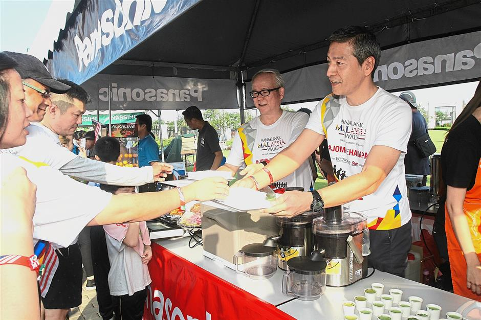 Uehara (right) serving fresh fruit juice at the company's booth after the walk. Helping out is Panasonic Malaysia Sdn Bhd marketing innovation department general manager Chew Keng Heng (second from right).