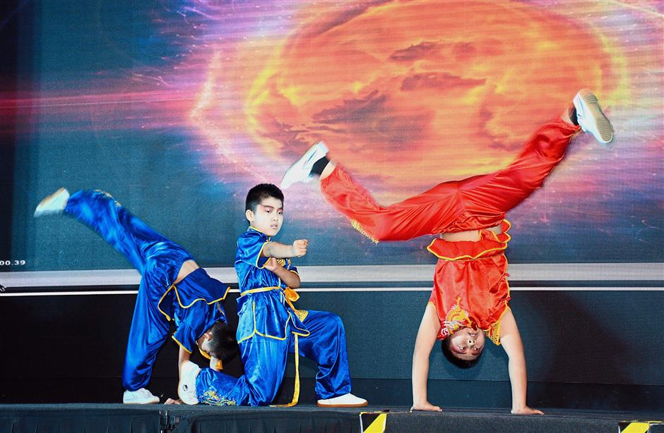 Young wushu exponents showing off their skills on stage.