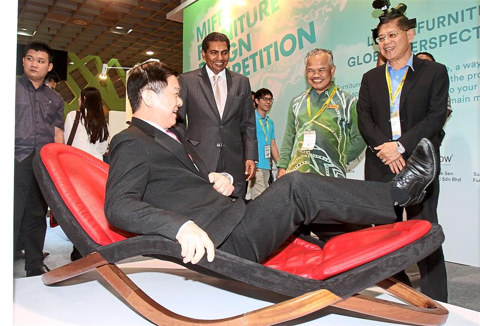 Just sit back: Lee testing out Wan Nurhanis' Infinity Lounge Chair design while MIFF chairman Datuk Dr Tan Chin Huat (right), Forest Research Institute Malaysia (FRIM) senior researcher officer Dr Rahim Sudin (second from right), and UBM Asia managing director (Asean Business) M. Gandhi (third from right) look on.