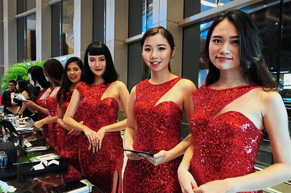 Pretty usherettes dressed in red welcoming guests at the launch of Gamuda Land's loyalty programme in the Grand Hyatt ballroom.