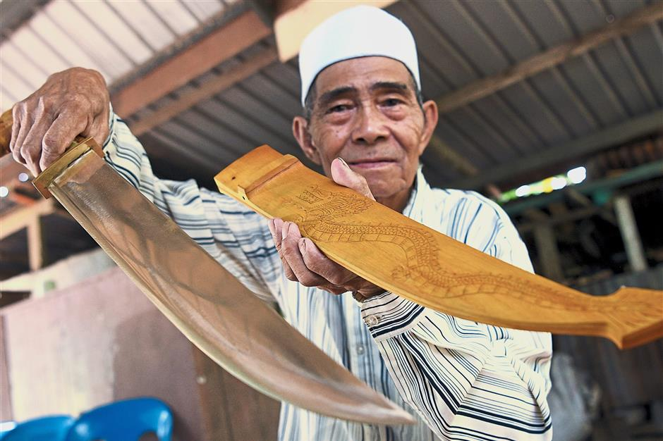 Ebin showing a copper parang and a sheath with a dragon motif.