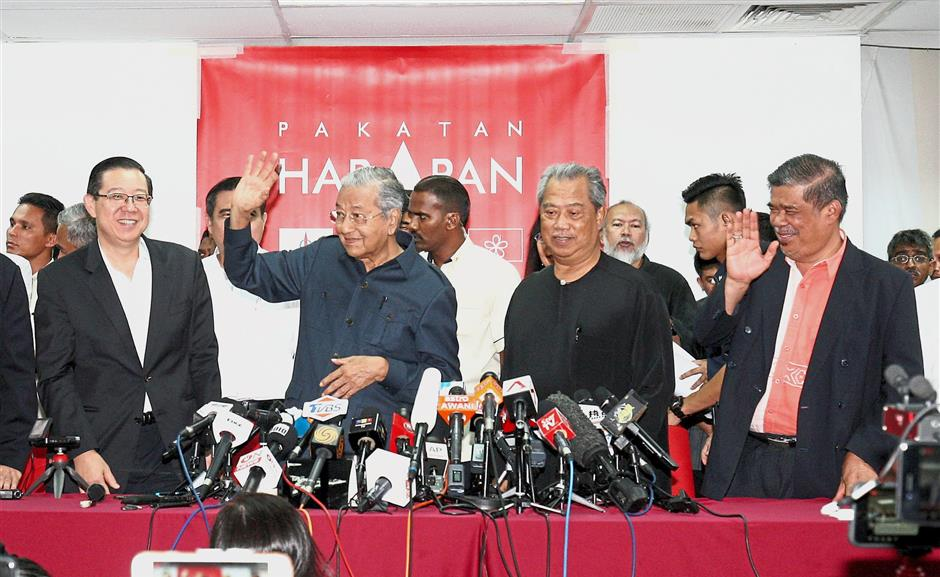 Fielding the press: Dr Mahathir waving to members of the media during the press conference at Menara Yayasan Selangor, Petaling Jaya. With him are (from left) Lim, Muhyiddin and Mohamad.