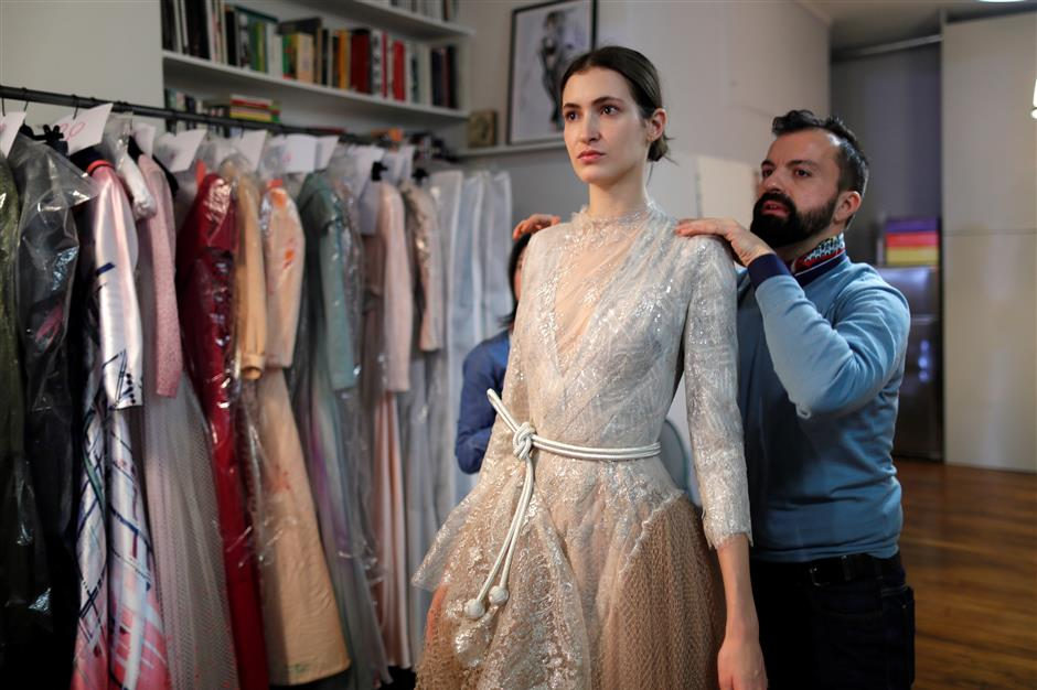 French designer Julien Fournie (R) adjusts a creation on model Greta (C) during a fitting at his workshop ahead of his Spring-Summer 2018 Haute Couture fashion show presentation in Paris, France, January 15, 2018. Picture taken January 15, 2018.  REUTERS/Charles Platiau