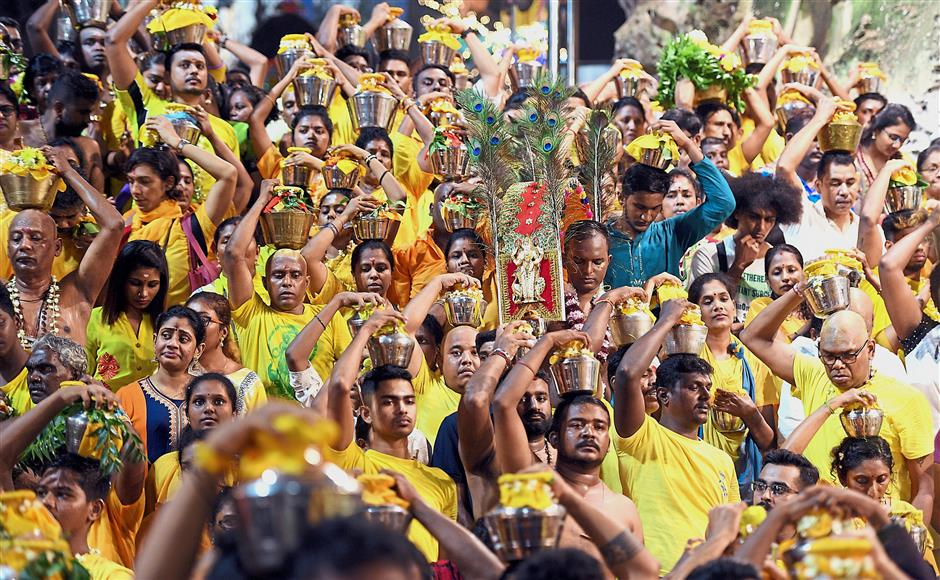 A day for prayers and penance: Devotees carrying kavadis and milk pots while walking towards the Batu Caves temple during Thaipusam.