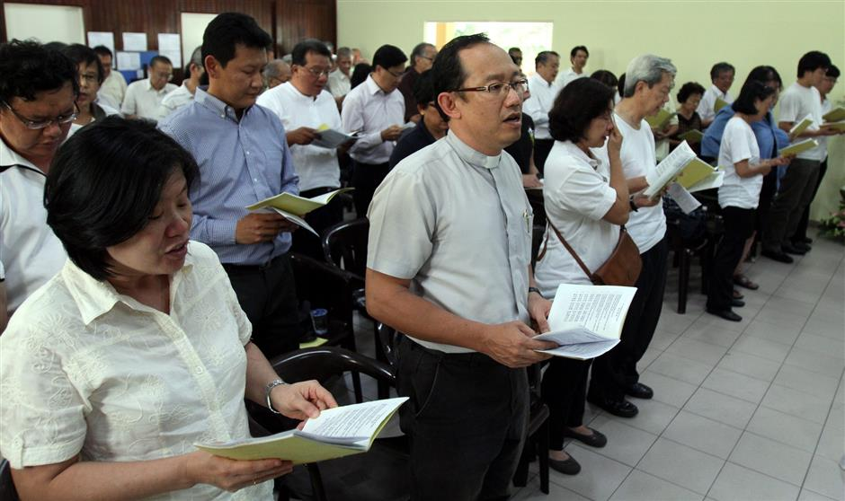 Friends and relatives offering prayers to the late Tan Jin Eong during the funeral service.