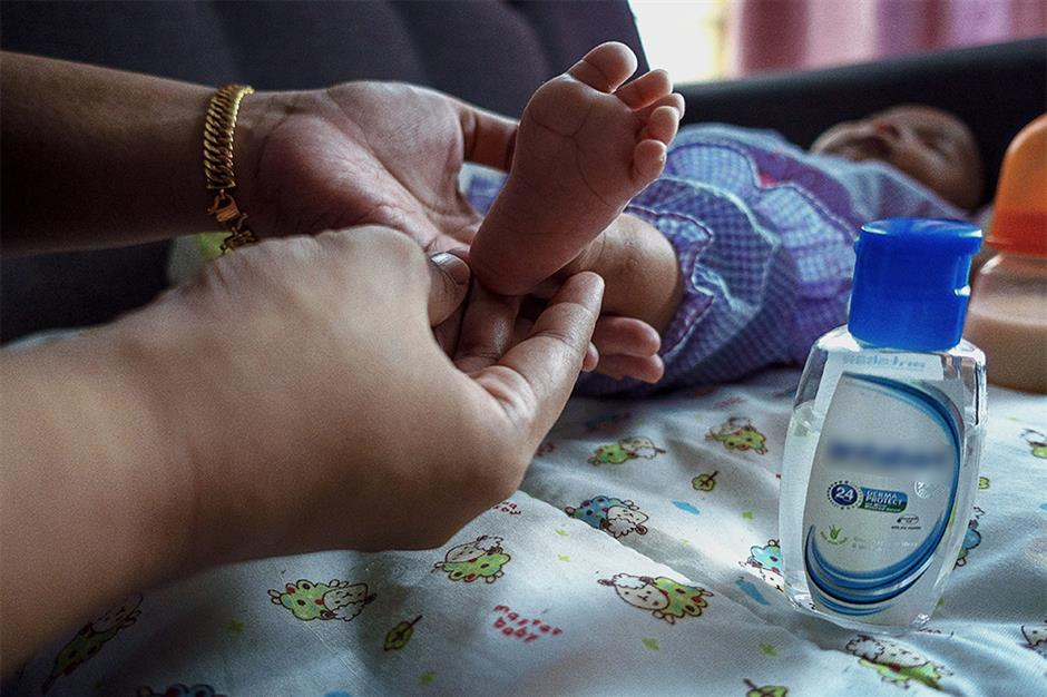 A woman checking for tell-tale signs of HFMD on her baby's foot.