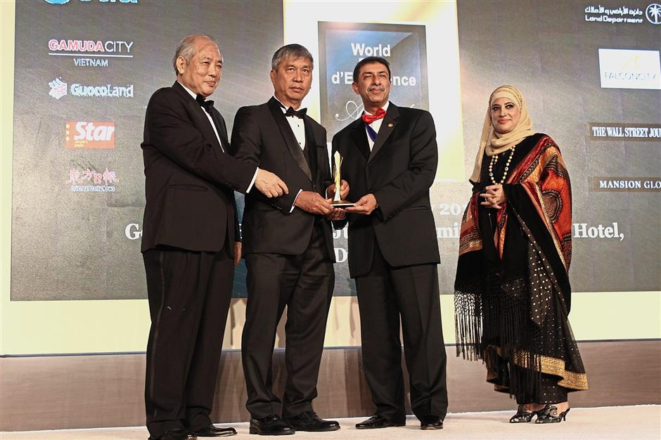 Farm Resort Gambang managing director Datuk Franky Chua Goon Eng receiving the World Gold Winner award (Environmental Rehabilitation Conservation Category) from Prof Chen (left) and Farook (second from right) for the Mangala Resort & Spa, Pahang project.