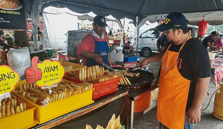 Khairil and Khairi frying the mini murtabak to attract buyers.