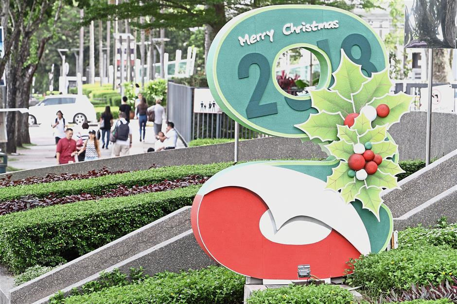 A mistletoe blooms against classic Christmas colours on G Hotel Gurney's G sign along Gurney Drive.