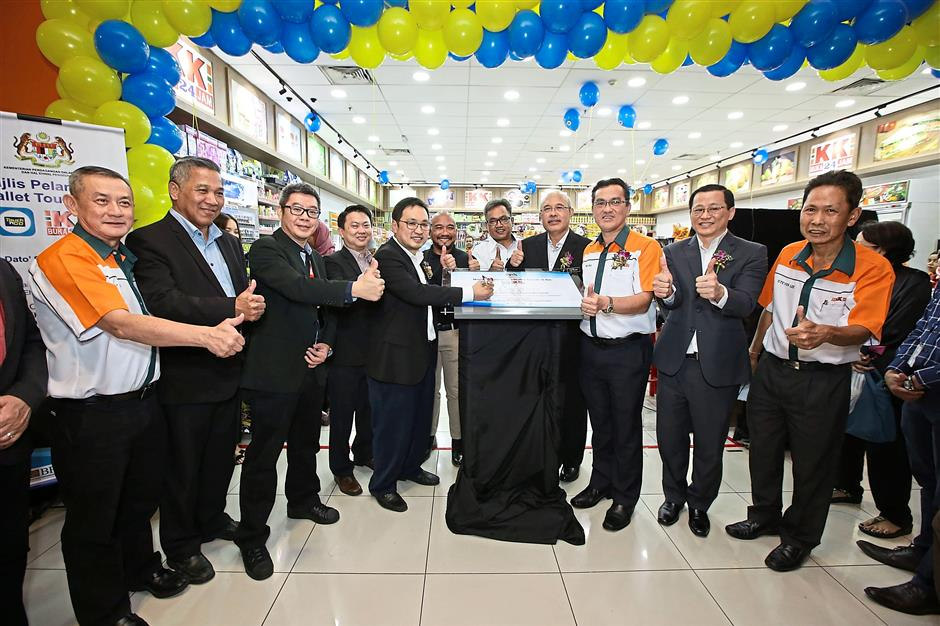 Domestic Trade and Consumer Affairs Deputy Minister Chong Chieng Jen (fifth from left) signing a plaque to signify the official partnership between KK Super Mart and the Touch 'n Go eWallet.