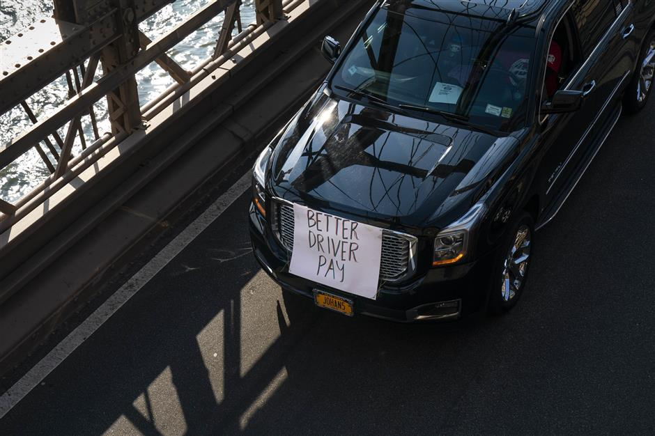 NEW YORK, NY - MAY 8: Members of the Independent Drivers Guild drive across the Brooklyn Bridge in protest against Uber and other app-based ride-hailing companies, May 8, 2019 in New York City. The protests in more than a dozen cities come ahead of Uber\'s anticipated Initial Public Offering on the New York Stock Exchange (NYSE) which could put the ride-hailing firm\'s calculation as high as $91.5 billion. Drivers are seeking higher wages and better rights as employees.   Drew Angerer/Getty Images/AFP == FOR NEWSPAPERS, INTERNET, TELCOS & TELEVISION USE ONLY ==