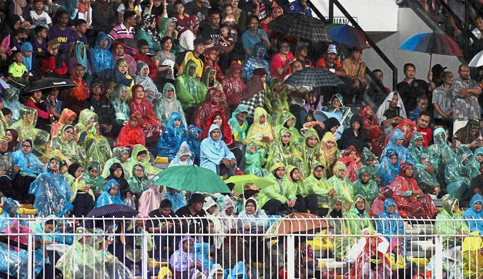 Some of the spectators in raincoats watching the opening ceremony of the 19th Sukma Games at Perak Stadium.