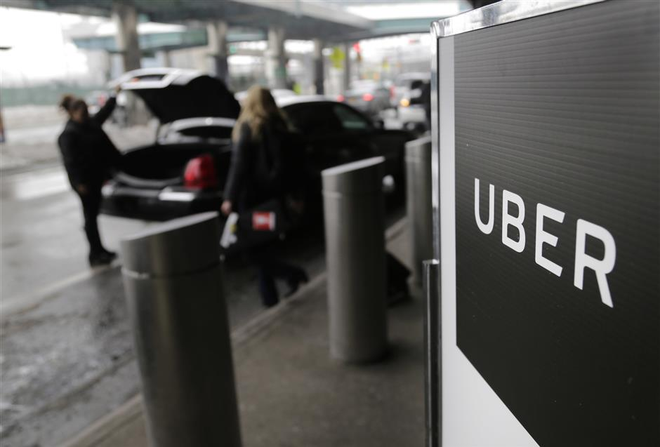 FILE - In this March 15, 2017, file photo, a sign marks a pick up point for the Uber car service at LaGuardia Airport in New York. Startup SURE says it has partnered with underwriter Chubb to launch a new service that allows Uber and Lyft ride-hailing passengers to buy accidental medical, death and dismemberment insurance coverage for the ride. The program, called RideSafe, works by connecting a customer\'s Uber or Lyft account to their SURE Insurance app, and once coverage is initially authorized, the passenger\'s ride is automatically insured. (AP Photo/Seth Wenig, File)