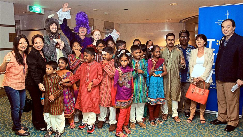 Children of Thangam Illam Welfare Society posing with the Pied Piper and other characters of The Mysterious Maestro show at The Petronas Philharmonic Hall, Suria KLCC