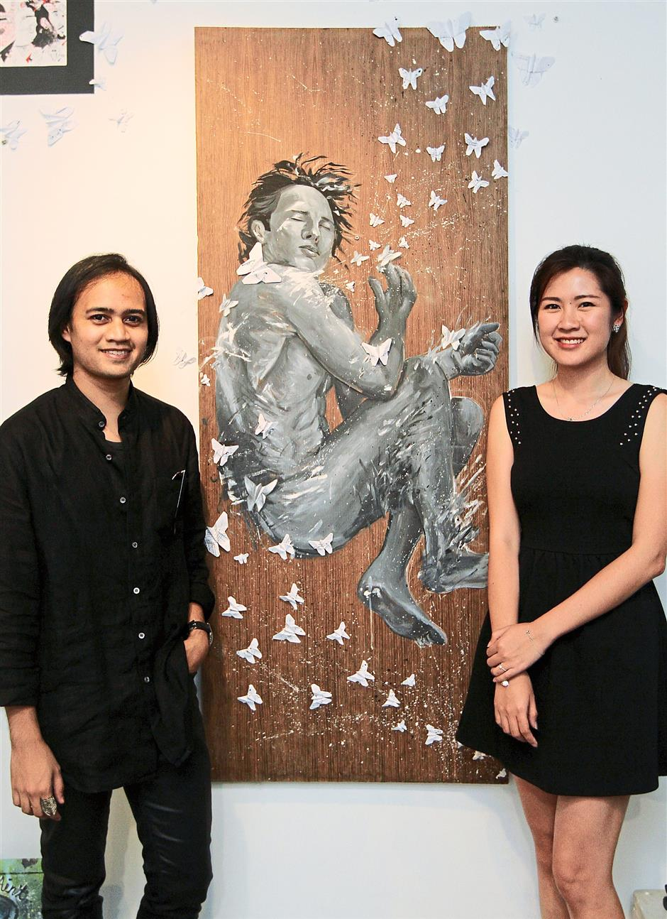 Pictured is an acrylic on plywood piece titled Nirvana by artist Caryn Koh Kooi San (right) and her best friend Aiman Ariffin (left) who himself is adept at origami folding though his background is in finance. The art piece itself is a representation of freedom from a sense of self within the dream-state as the male in the portrait is stripped bare in foetal position while the origami butterflies that represents beauty, escapism but also a contrasted sense of responsibilities that border the dream and reality.